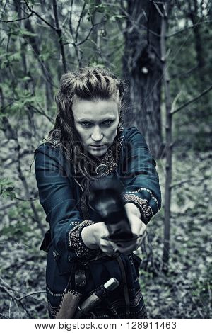 Serious scandinavian woman with sword posing in a forest