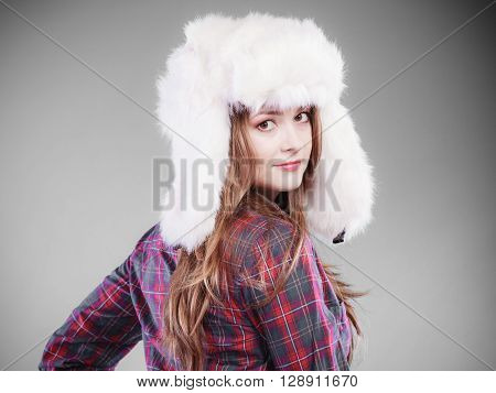 Winter fashion. Close up young woman wearing fashionable wintertime clothes white fur cap studio shot on gray background.