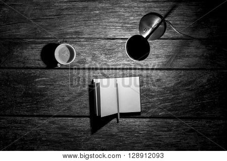 Top view of lit desk lamp open notebook with pencil and cup of coffee on a textured wooden work desk monochrome image.