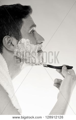 Young man shaving using razor with cream foam. Handsome guy removing face beard hair. Skin care and hygiene. Black and white bw photo.