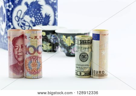 Chinese yuan currency American money and European Union euro stand in front of Asian porcelain tea cups and storage jar suggesting Asian meeting and business finance discussions.