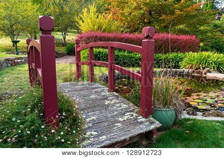 Wooden bridge over a pond in an autumn park. Bisley garden Mount Wilson Australia
