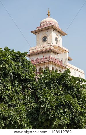 View of the famous City Palace in Jaipur, Rajasthan, which was the residence of the Kachwaha Rajput clan. The palace tower is seen on the background with lush green trees.