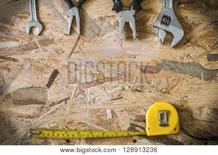 The working tools for construction and repair of house: tape measure (yardstick), wrench, pliers, spanner. Photo with copy space and vignetting effect.