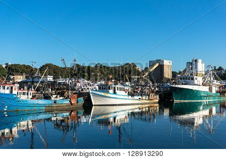 Fishing boats trailers at port at day against clear blue sky on the background