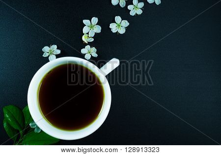 white cup of black tea with cherry blossoms and green leaf on black background from above. top view