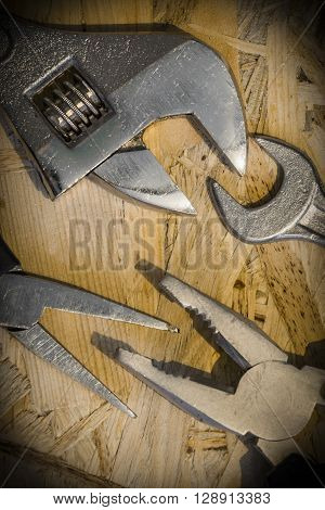 The working tools for construction and repair of house: monkey wrench (screw wrench), pliers, spanner. Photo with vignetting effect. Vertical orientation. Close-up.