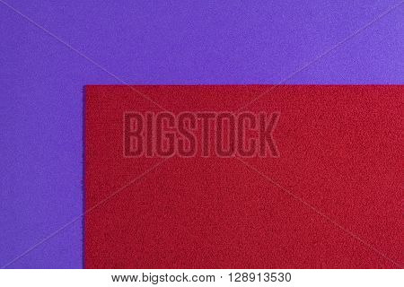 Eva foam ethylene vinyl acetate sponge plush red surface on purple smooth background