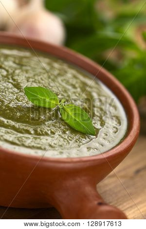 Fresh pesto made of basil and spinach in a rustic bowl garnished with fresh basil leaf (Selective Focus Focus on the basil leaf on the pesto)