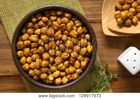 Chickpeas roasted with thyme oregano salt and pepper photographed overhead on wood with natural light (Selective Focus Focus on the chickpeas)