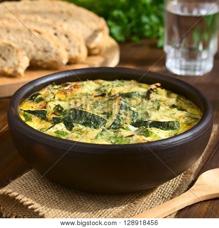 Frittata with zucchini and parsley in rustic bowl photographed with natural light (Selective Focus Focus one third into the first frittata)