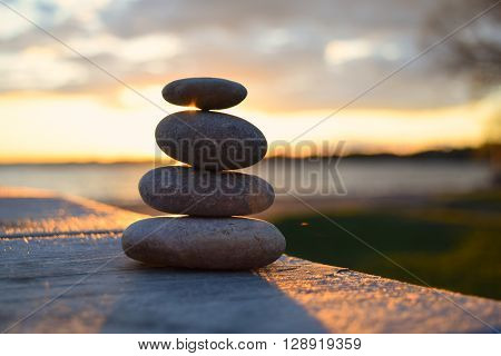 Balanced rocks during a sunset by a lake.