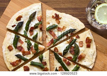 Green asparagus and bacon tarte flambee or Flammkuchen a typical Alsatian and South German dish photographed overhead on wooden board with natural light
