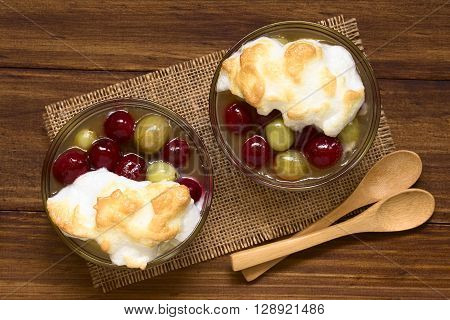 Stewed red and green gooseberry dessert with meringue in glass bowls with spoons on the side photographed overhead on dark wood with natural light