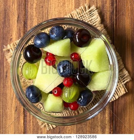 Fresh fruit salad made of cantaloupe melon blueberry redcurrant gooseberry and sweet cherry in glass bowl photographed overhead on dark wood with natural light