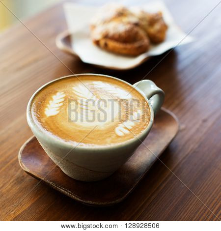 square photo of beautiful coffee latte art and sweet pastry in the background cafe concept