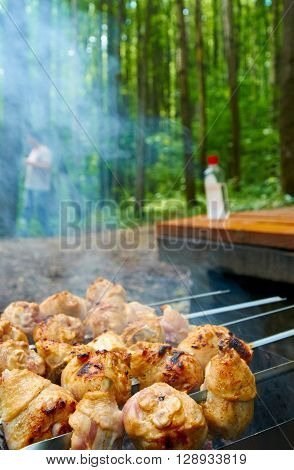 Barbecue grill with meat close-up, with a bottle of flammable liquid