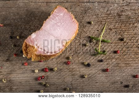 Smoked pork loin with spices over wooden background