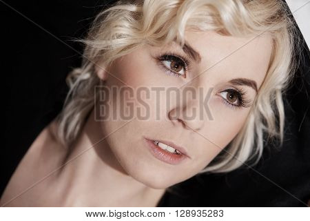 Closeup portrait of young blonde woman, looking away.