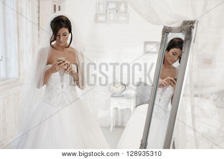 Beautiful bride using mobilephone in white bedroom.