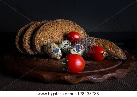 Fresh bread on wooden tablevintage filter Traditional black rye-bread on dark background Red cherry tomatoes with sliced bread and quail eggs vintage still life
