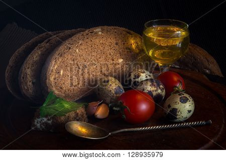 Fresh bread on wooden tablevintage filter Traditional black rye-bread on dark background Red cherry tomatoes with sliced bread and quail eggs and glass of olive oil and spoon vintage still life