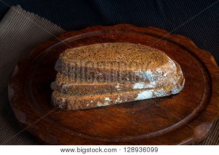 Fresh bread on wooden tablevintage filter Traditional black rye-bread on dark background sliced bread vintage still life