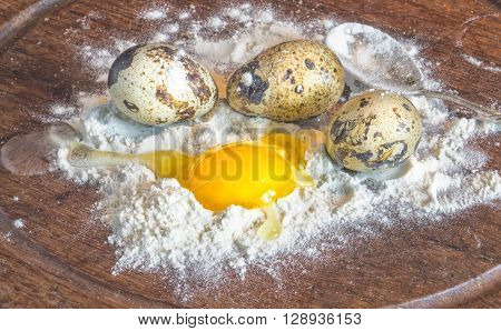 quail eggs and flour Quail eggs with one broken egg and spoon on wooden kitchen table rustic vintage