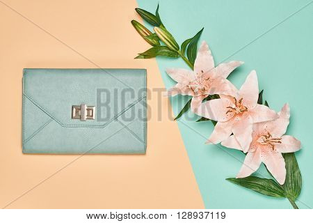 Fashion woman accessories set. Glamor stylish handbag clutch and summer lily flowers. Elegant trendy girl. Unusual creative look. Overhead, romantic. Top view, vanilla pastel background
