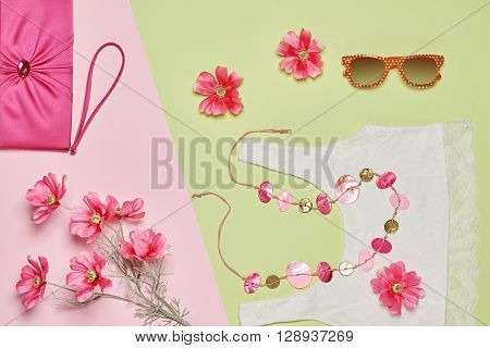 Summer Fashion woman clothes accessories set. Glamor lace top, stylish necklace, handbag clutch, sunglasses, pink flowers. Unusual creative elegant look. Overhead, romantic.Top view, green background