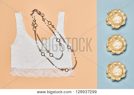 Fashion woman clothes accessories set. Glamor lace top, stylish necklace and summer flowers. Elegant trendy outfit. Unusual creative girl. Overhead, romantic. Top view, vanilla pastel background