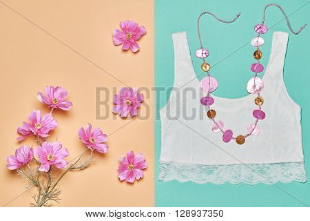 Fashion woman clothes accessories set. Glamor lace top, stylish necklace and summer pink flowers. Elegant trendy date outfit. Unusual creative girl. Overhead, romantic.Top view, vanilla background
