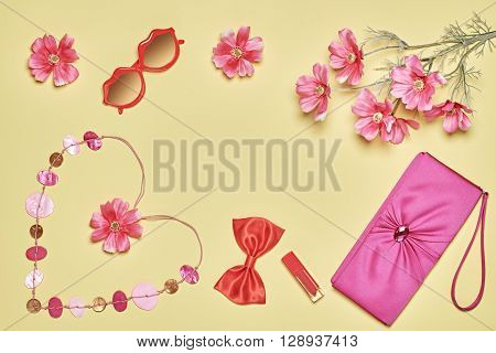 Stylish handbag clutch, red sunglasses, lipstick, bow, necklace and summer flowers. Woman essentials fashion accessories set. Creative romantic background, yellow. Overhead, modern still life.Top view