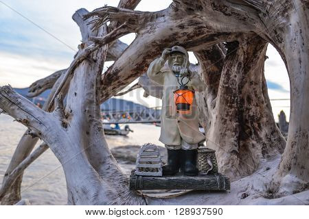 Lobster fisherman statue with lit solar lantern on beach with driftwood