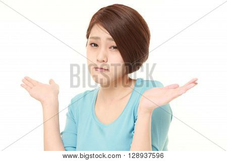 portrait of young Japanese woman confused on white background