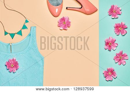 Summer Fashion Ladies clothes accessories set. Glamor blue dress, stylish shoes, necklace, pink flowers. Unusual creative modern elegant look. Overhead, romantic outfit. Top view, yellow background