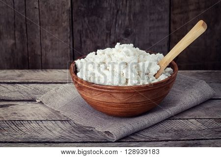 dairy product cottage cheese in brown ceramic bowl. Curd in brown bowl on sacking. Fresh cottage cheese in bowl with spoon on vintage wooden table