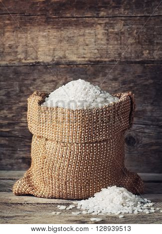 white rice in burlap bag with pile of rice grain on wood background