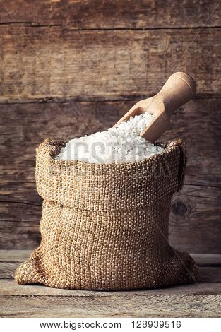 raw white rice in burlap bag with scoop on wooden background. Full sack with rice