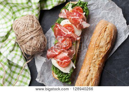 Ciabatta sandwich with romaine salad, prosciutto and mozzarella cheese over stone