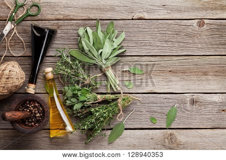 Fresh garden herbs and condiments on wooden table. Oregano, thyme, sage, rosemary. Top view with copy space