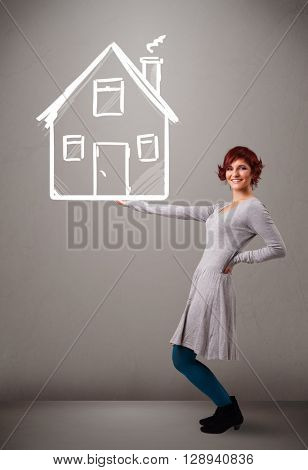 Beautiful young lady holding a huge drawn house