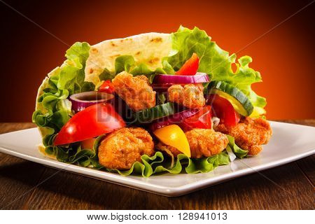 Chicken nuggets and vegetables in tortilla wrap