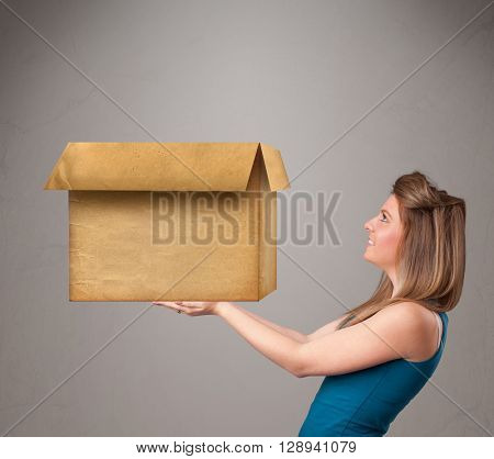 Beautiful young woman holding an empty cardboard box