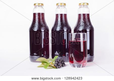 Three bottles of syrup made from aronia berries and glass