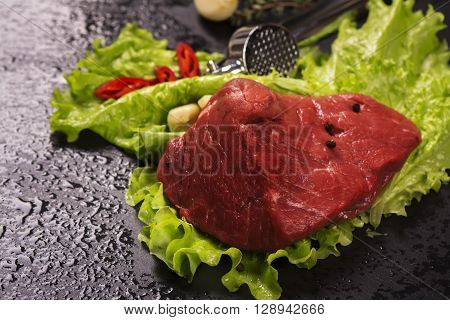 Raw meat with lettuce, garlic, chili peper and thyme over black stone table