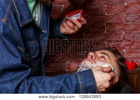 Shaving in the client Barbershop. Berber shaves client