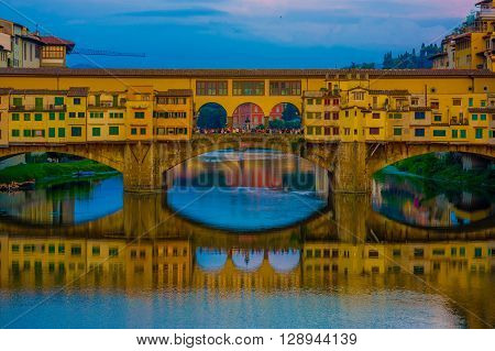 FLORENCE, ITALY - JUNE 12, 2015: The Old Bridge and Vasari Corridor in Florence, shops and turists on the middle of the Bridge. Shadow in the Arno river.