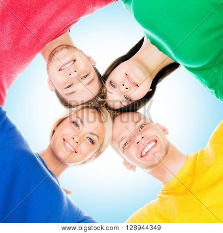 Happy students in colorful clothing standing together over blue sky background
