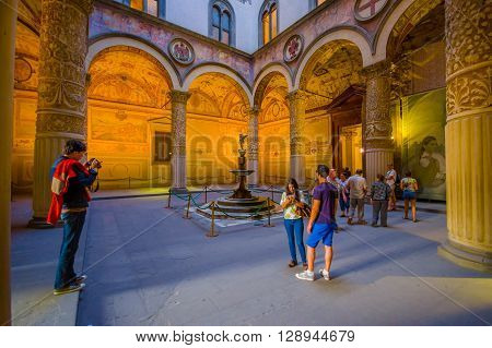 FLORENCE, ITALY - JUNE 12, 2015: Turists walking around main yard of Old Palace or Palazzo Vecchio in Florence, angel statue on the middle